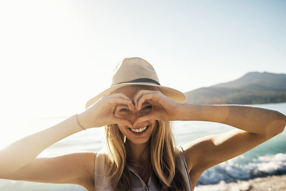 Woman smiling creating love heart sign in front of eyes at the beach