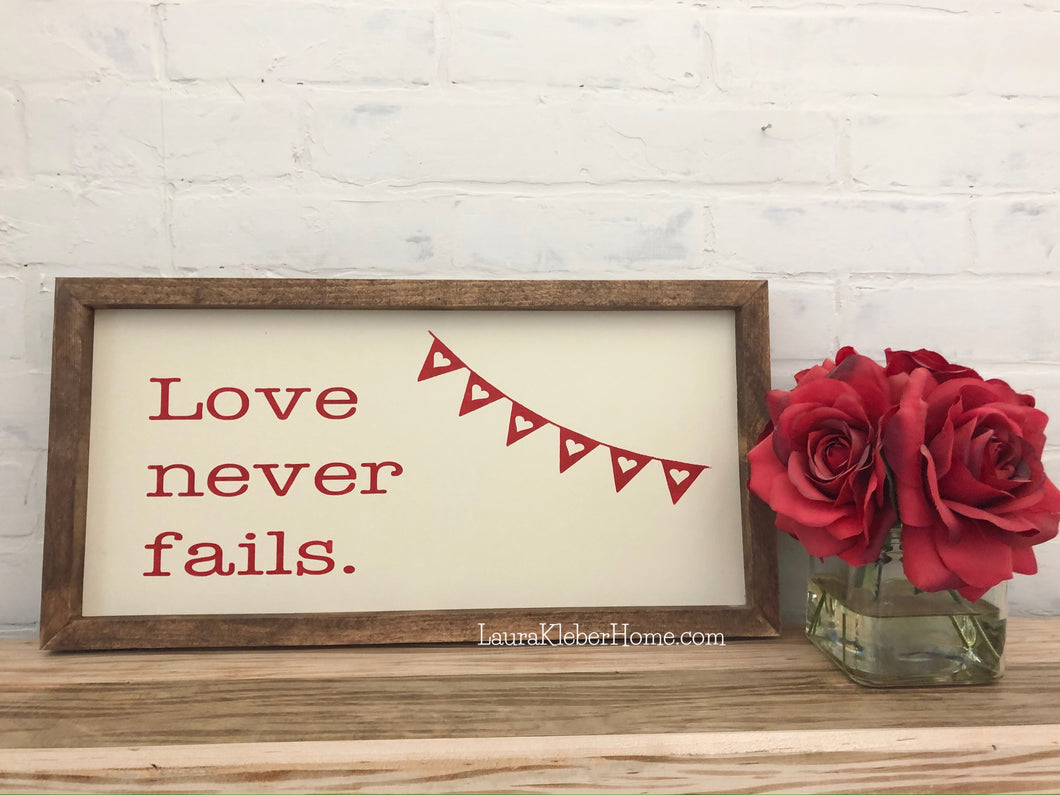 A 10x18 inch framed wood sign with love never fails painted in red with a white background.