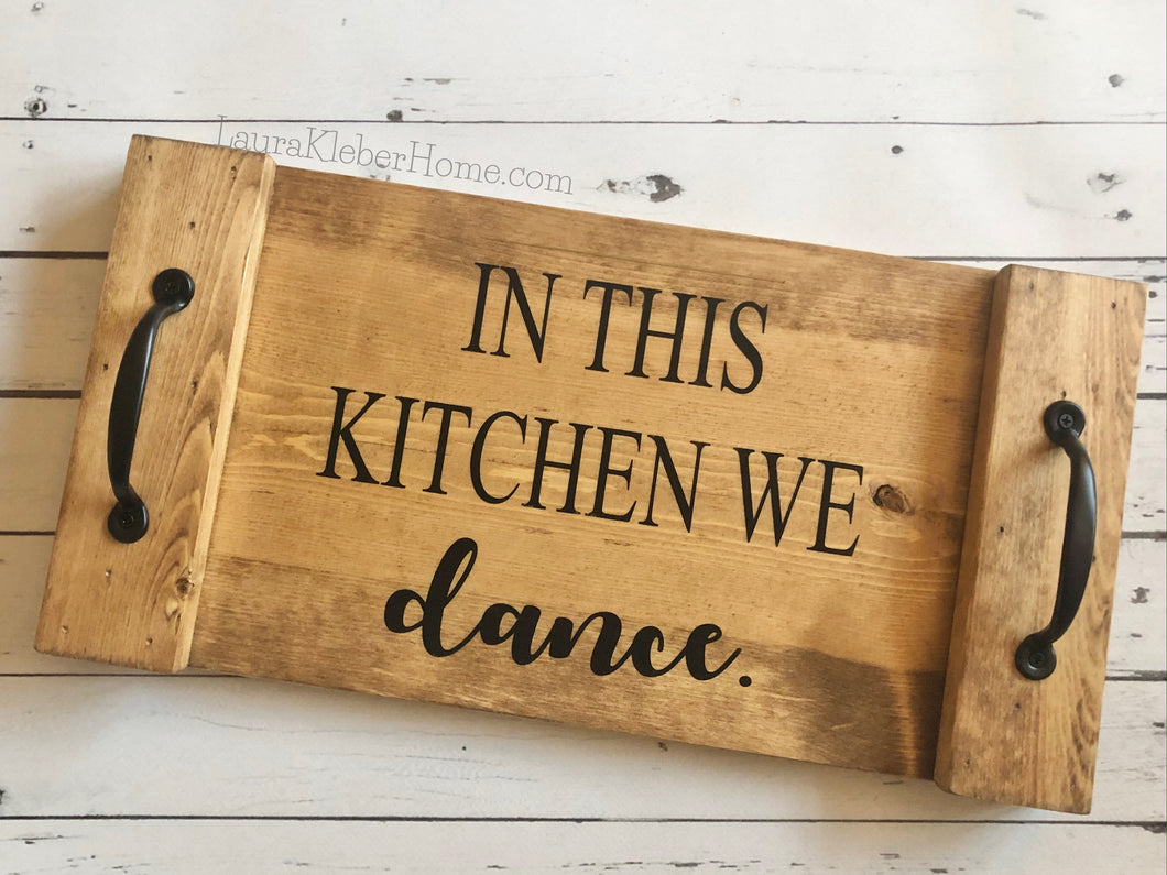 A 10x18 inch wood tray completed in Early American stain with the words In this kitchen we dance in black with black metal handles.