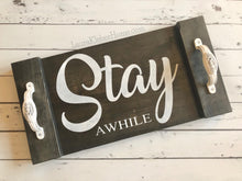 Load image into Gallery viewer, A 10x18 inch wood tray, hand made and hand painted. Black stained and words 'Stay Awhile' painted in white with white metal decorative handles on ends.