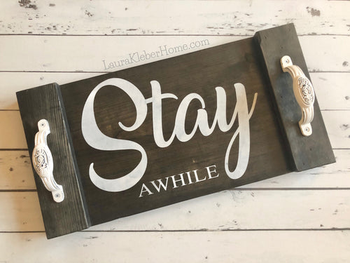A 10x18 inch wood tray, hand made and hand painted. Black stained and words 'Stay Awhile' painted in white with white metal decorative handles on ends.