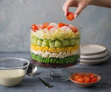 Layered vegetable salad with creamy herb dressing
