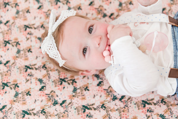 Baby laying on floral modern nursery crib sheet