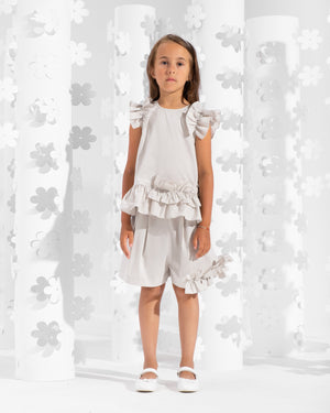 Sleeveless top trimmed with asymmetrical frills