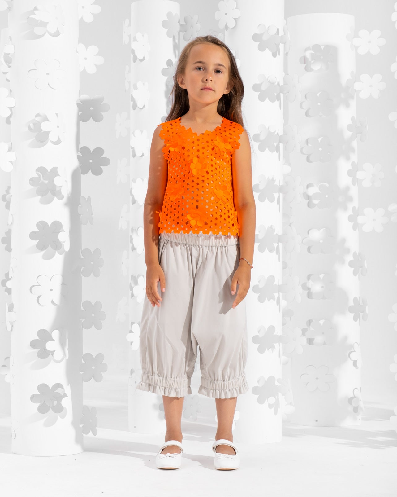 Sleeveless laser-cut top decorated with floral appliques