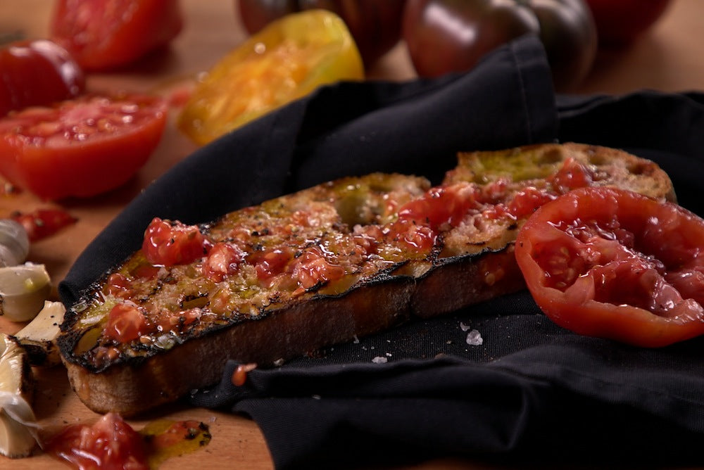 Catalan grilled tomato bread garnished with slices of tomato