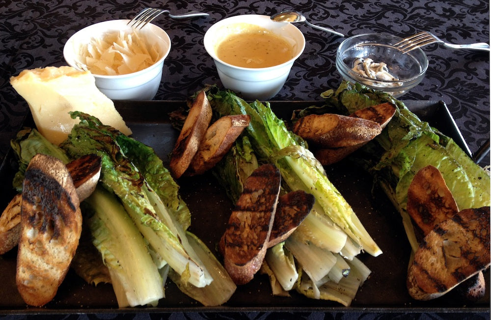 4 bunches of grilled romaine with grilled bread, parmesan and dressing on the side