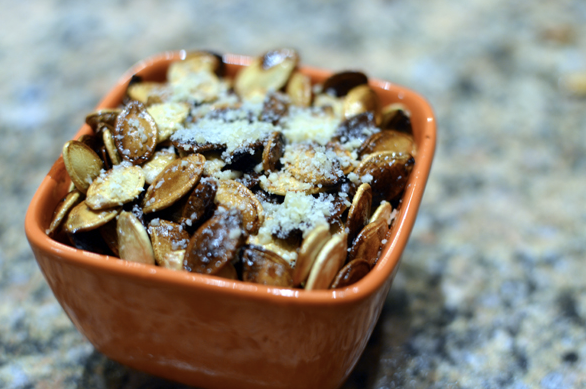 grilled pumpkin seeds with parmesan in terra cota dish