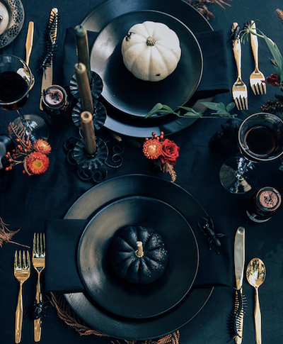 2 black place settings with white and black pumpkins and gold silverware