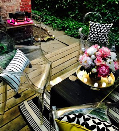 Patio garden with black and white graphic pillows and clear acrylic chairs