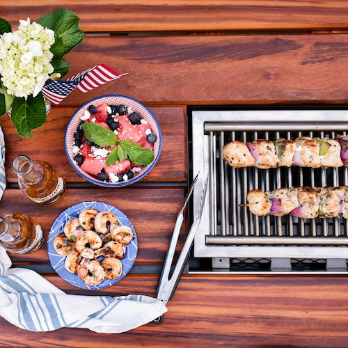 angara grill table with kebobs grilling and American flag