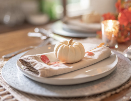 one mini white pumpkin centered on a folded linen napkin on plate
