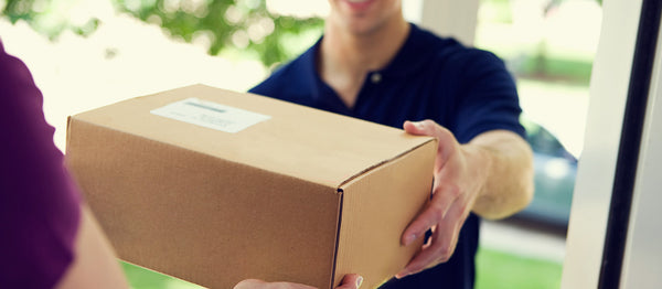 Delivery man delivering a discreete box to a customer at home