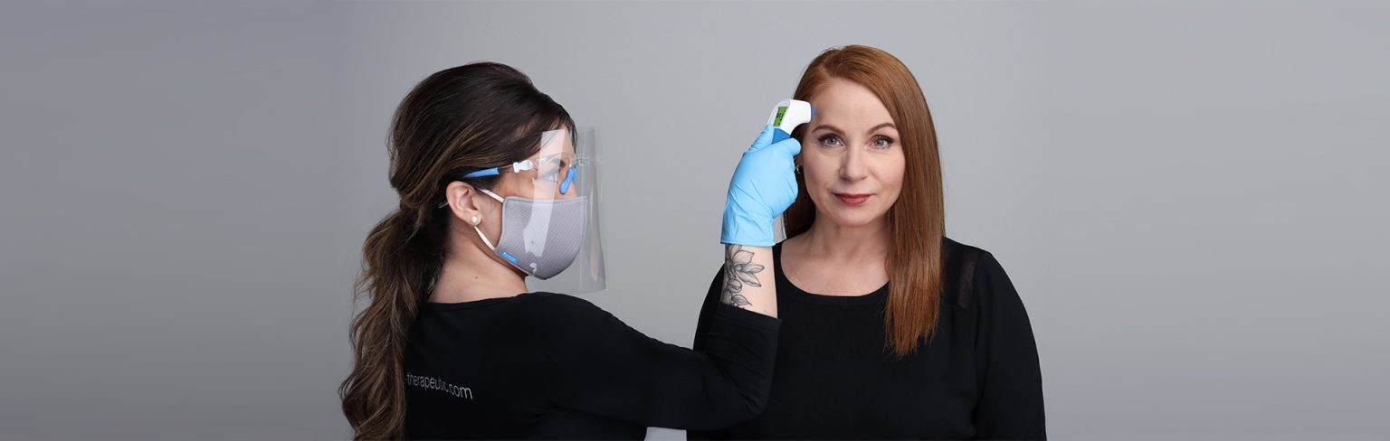 Image of Esthetician Wearing a mask and using a Thermometor on a client with red hair who is wearing a black shit.
