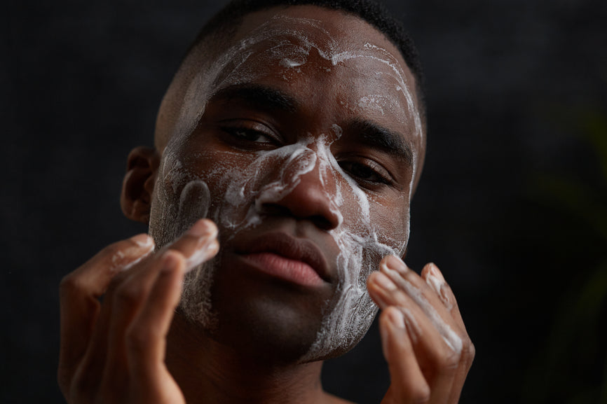 photo of a man washing his face with a facial cleanser and looking straight at the camera with a black background