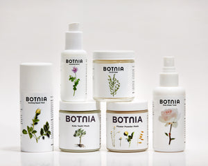 photo of six botnia skincare products, the hydrating serum, gentle cleanser, three masks and the rose water toner, with a white/grey background and light shadows.