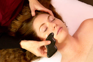 beautiful redhead getting facial gua sha performed on her in Pasadena. Esthetician is using a dark green gua sha stone.