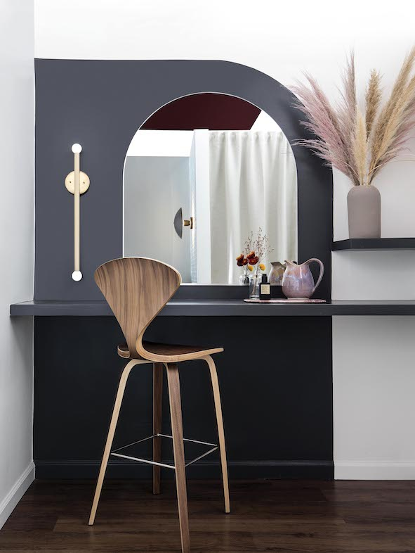 Photo of a vanity at Cheeks & Co in Old Pasadena. There is a rounded mirror, wall sconce and stool to sit on after your facial.