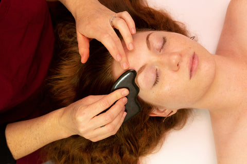overhead shot of redhead in pasadena getting gua sha performed on her eye area using a dark green gua sha stone.