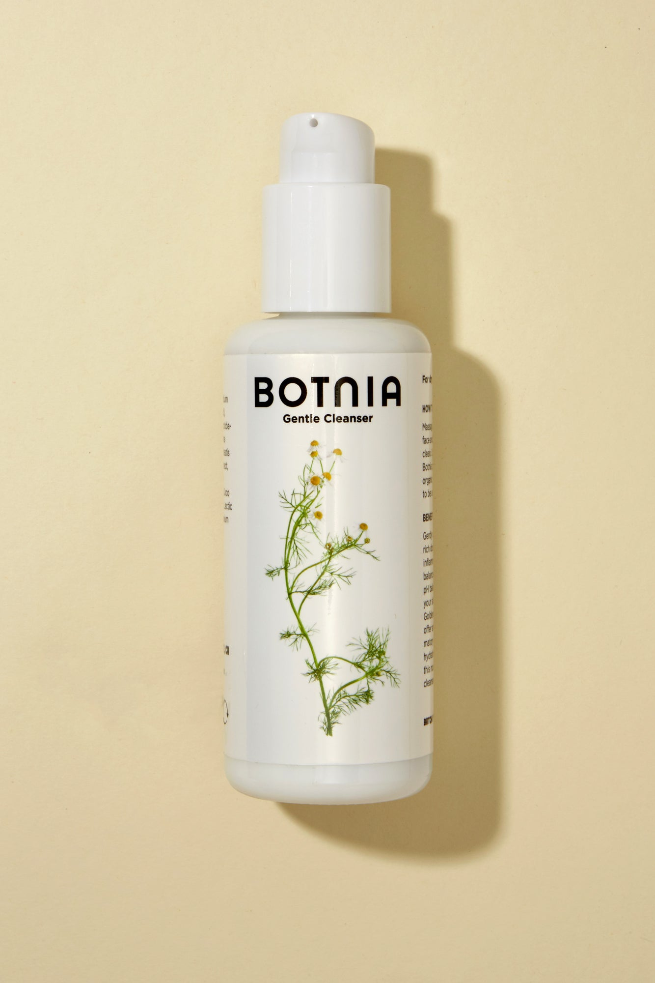 overhead picture of botnia gentle cleanser in new updated glass bottle. On a tan background. Bottle is white with a label and picture of a flower on the front.