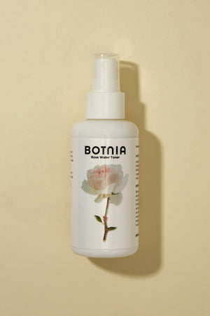 photo of botnia's rose water toner in a glass bottle with a picture of a rose on the front of the bottle. There is a small shadow to the right and the background is tan.