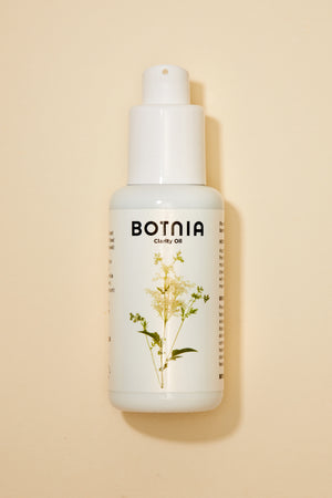 overhead shot of Botnia's clarity oil on a tan background with a light shadow on the right hand side.