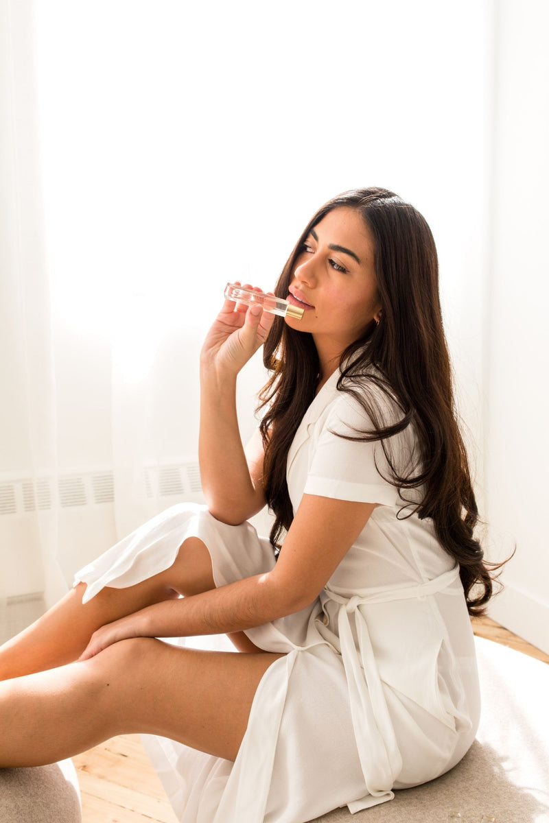 Girl in white dress holding essential oil roller in 10ml size.