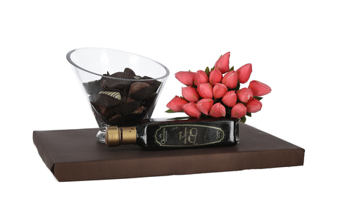 Stunning glass bowl filled with Belgian chocolates, bottle of chocolate liquor, and bouquet of fake tulips