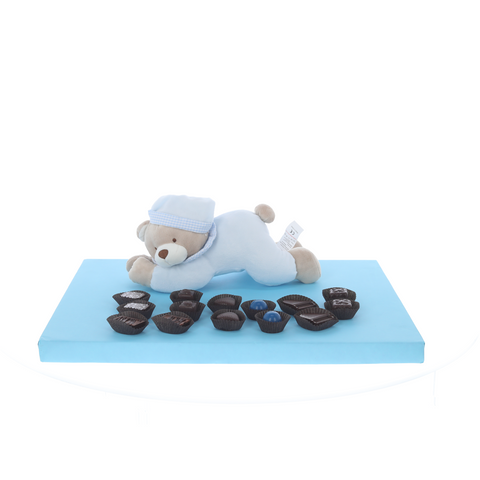 Blue lying teddy with display of Belgian chocolates