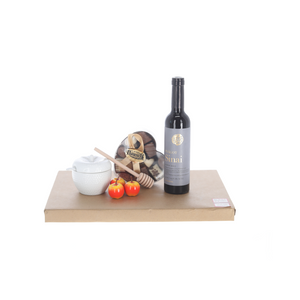 White ceramic apple-shaped honey dish with chocolates and wine