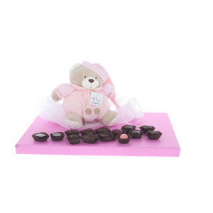 Plush baby toy with music playing pull-string surrounded by delicious Belgian pralines - Girl