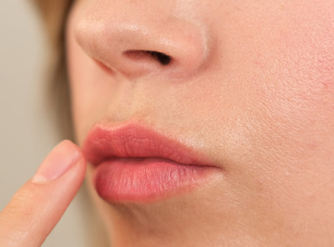 Woman applying cream blush to lips