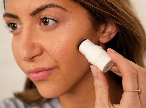 Woman applying bronzer to contour her face.