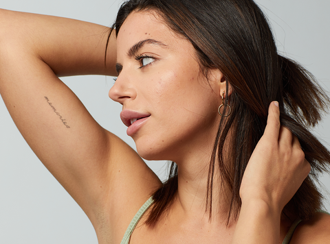 Audrey from Undone Beauty in minimalist makeup look showing her tattoo.