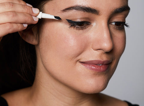 Undone Beauty Unscripted Eyeliner and model creating a cat eye look