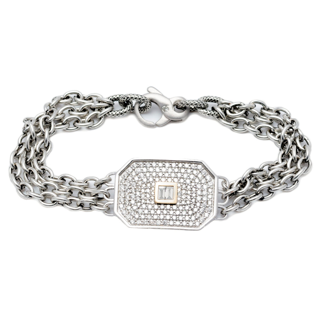 This triple-strand bracelet features a satin-finish, sterling silver, chamfered rectangle covered in diamond pavé and accented by two baguette diamonds bezel-set in 14K yellow gold in the center on our exclusive steel chain.  Includes a Liza Beth signature satin finish diamond clasp  Dimensions of rectangle: 25 mm x 18 mm  Total diamond carat weight: 1.47 ct  Made in USA