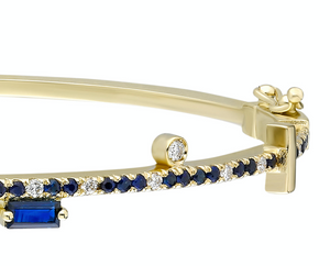Blue sapphire and 14k yellow gold bangle with double clasp Blue sapphire: .57CT  White diamonds: .16CT  Blue sapphire trillion: .42CT  Blue sapphire baguette: .16CT  Made in Turkey