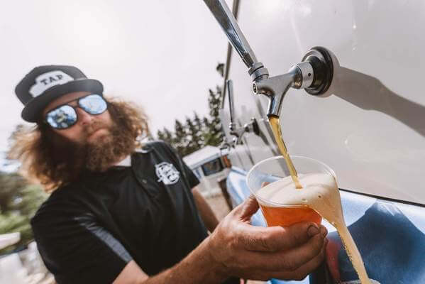 Mobile bartender pouring fresh draft beer from vintage blue truck.