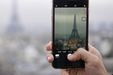 close-up of a hand holding an iphone and taking picture of eiffel tower