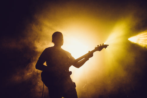 guitarist silhouette on a stage in smoke and backlights