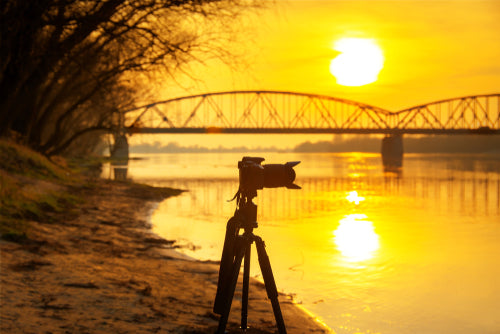 silhouette of the camera on tripod with amazing sunset in background