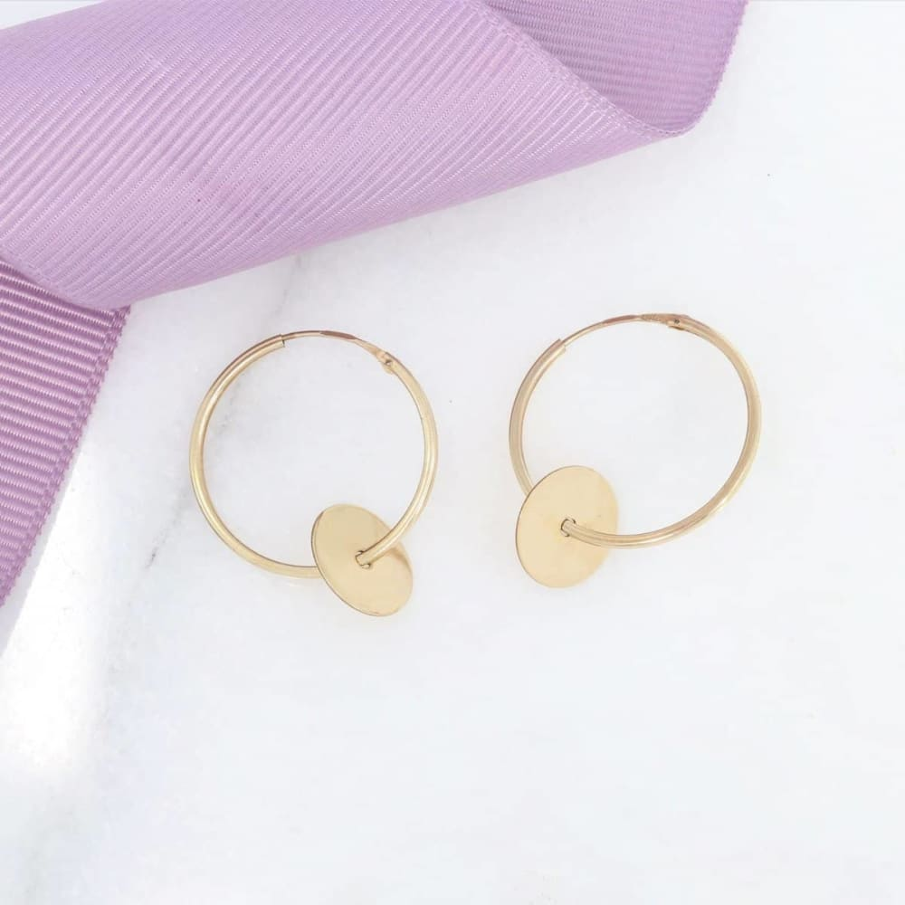 Woman wearing 9ct gold hoop earrings