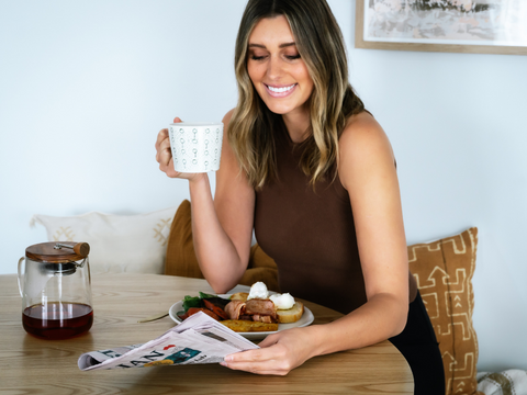 Image of a young woman drinking tea along with her breakfast while reading a newspaper