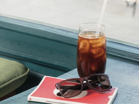 Cold Brew Tea in a Tall Glass with ice - a book and a pair of sun-glasses