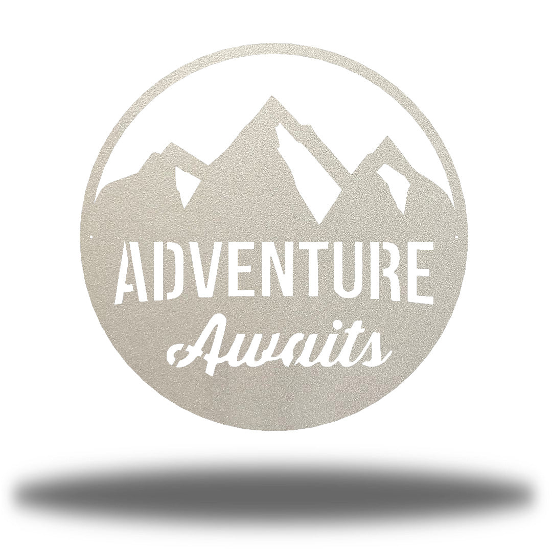 "Silver steel decorative signage with mountain designs and the text ""ADVENTURE Awaits"" laser cut through it"