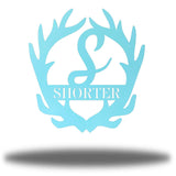 "Light blue antler-shaped steel decorative monogram with the initial ""S"" in the middle and the word ""SHORTER"" below it."
