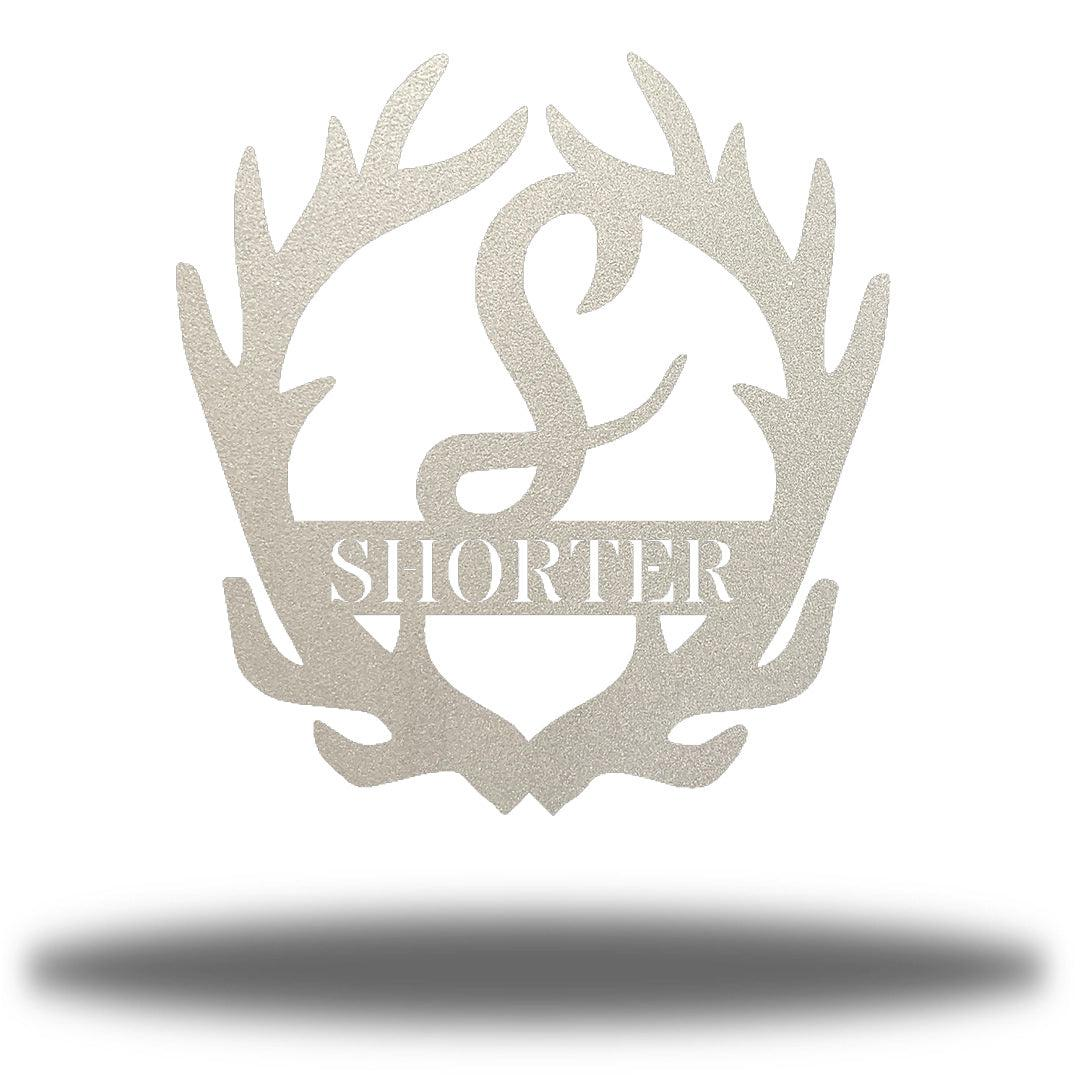 "Silver antler-shaped steel decorative monogram with the initial ""S"" in the middle and the word ""SHORTER"" below it."