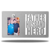 "Silver decorative picture board sign with a photo of a man and an older man along with the texts ""FATHER, HUSBAND, HERO"""