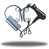 "Black heart-shaped steel monogram featuring comb, blower, scissors and the initial ""M"""