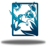 Teal steel wall art decoration that features a hummingbird feeding on flowers design